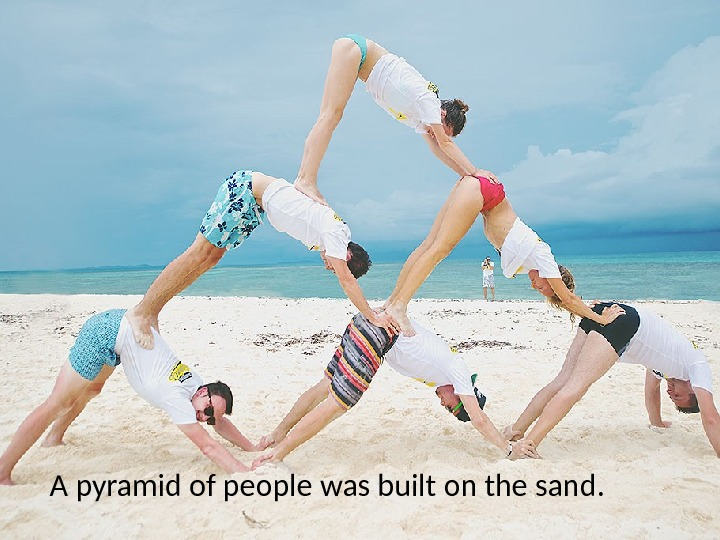A pyramid of people was built on the sand.