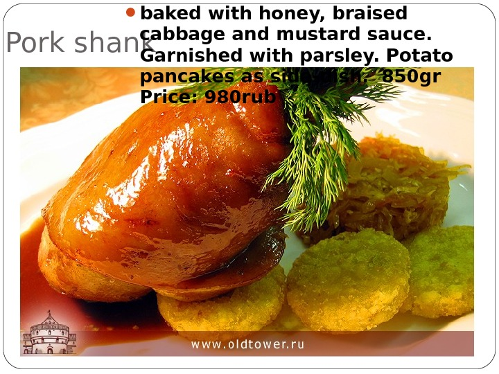 Pork shank  baked with honey, braised cabbage and mustard sauce.  Garnished with parsley. Potato