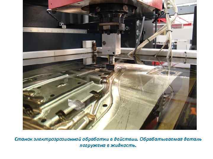 Станок электроэрозионной обработки в действии. Обрабатываемая деталь погружена в жидкость.