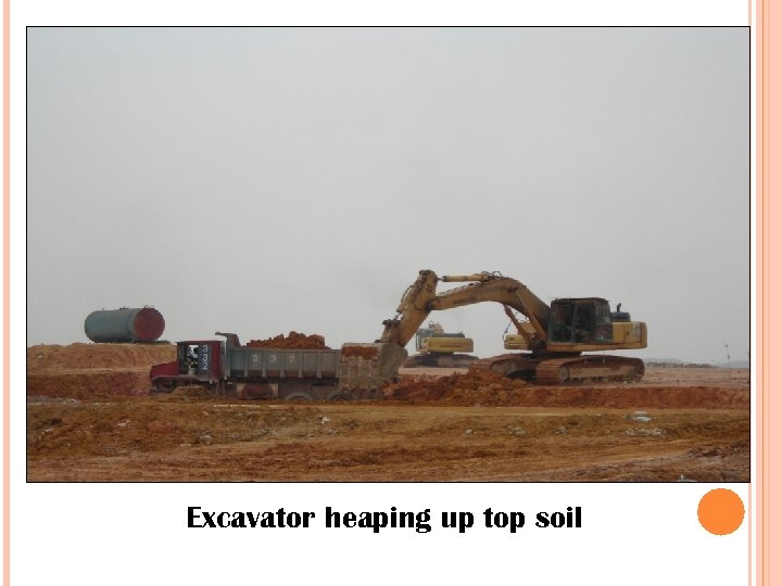 Excavator heaping up top soil