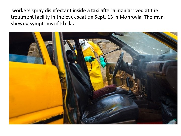 workers spray disinfectant inside a taxi after a man arrived at the treatment