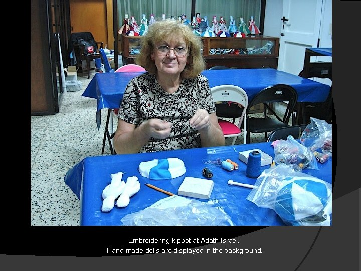 Embroidering kippot at Adath Israel. Hand made dolls are displayed in the background.