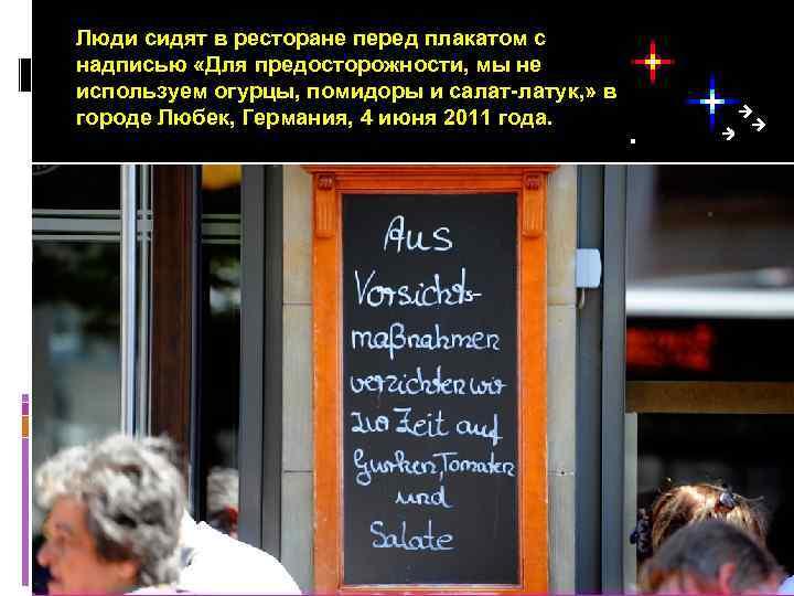 Люди сидят в ресторане перед плакатом с надписью «Для предосторожности, мы не используем огурцы,