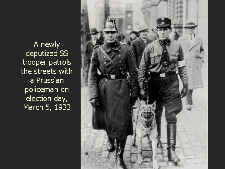A newly deputized SS trooper patrols the streets with a Prussian policeman on election