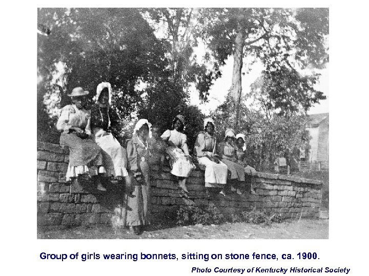 Group of girls wearing bonnets, sitting on stone fence, ca. 1900. Photo Courtesy of