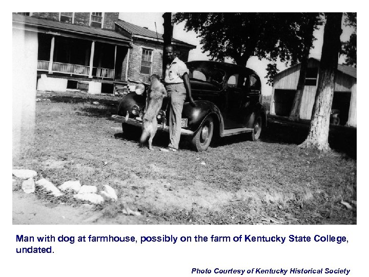 Man with dog at farmhouse, possibly on the farm of Kentucky State College, undated.