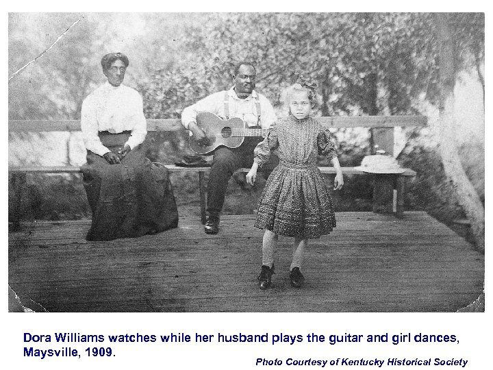 Dora Williams watches while her husband plays the guitar and girl dances, Maysville, 1909.