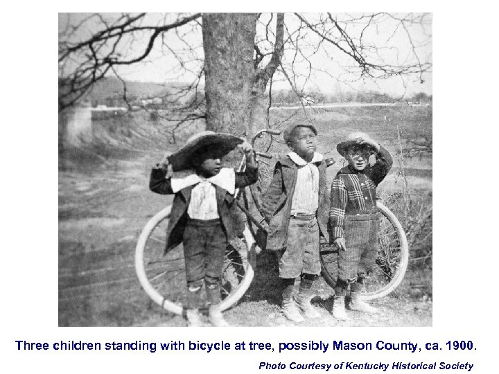 Three children standing with bicycle at tree, possibly Mason County, ca. 1900. Photo Courtesy