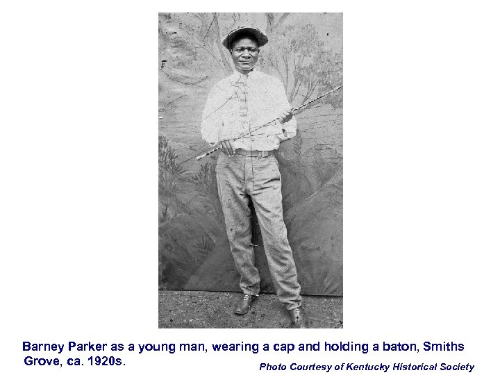 Barney Parker as a young man, wearing a cap and holding a baton, Smiths