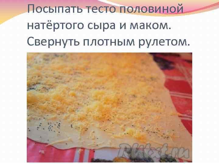 Посыпать тесто половиной натёртого сыра и маком. Свернуть плотным рулетом.