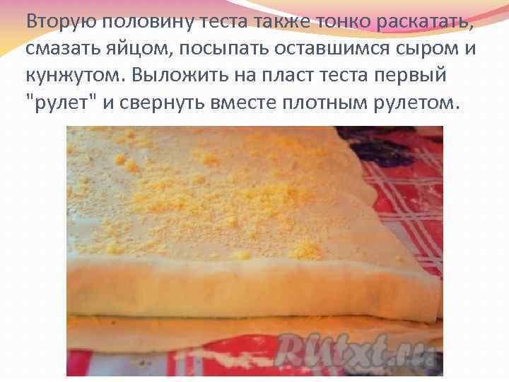 Вторую половину теста также тонко раскатать, смазать яйцом, посыпать оставшимся сыром и кунжутом. Выложить