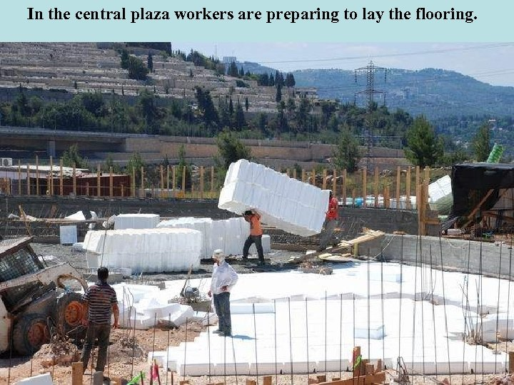 In the central plaza workers are preparing to lay the flooring.