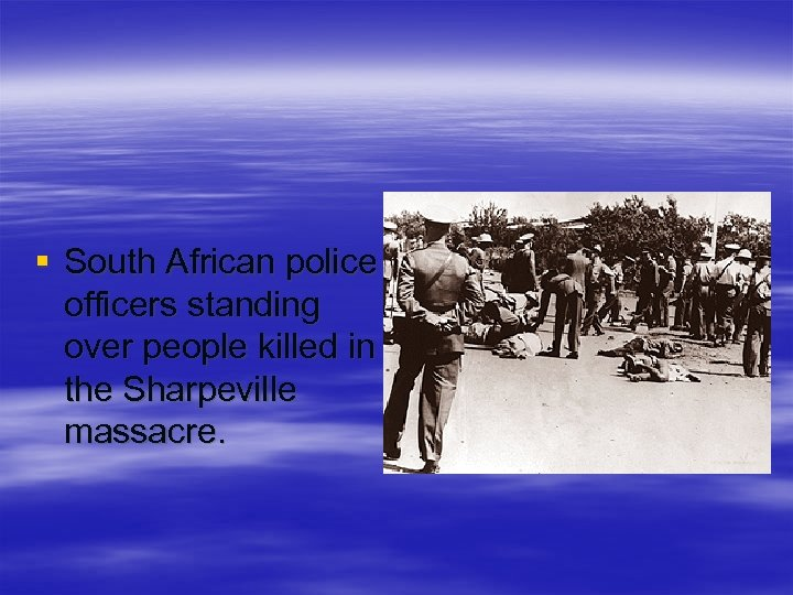 § South African police officers standing over people killed in the Sharpeville massacre.