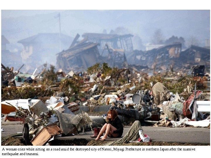 A woman cries while sitting on a road amid the destroyed city of Natori,