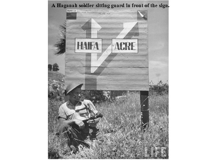 A Haganah soldier sitting guard in front of the sign.