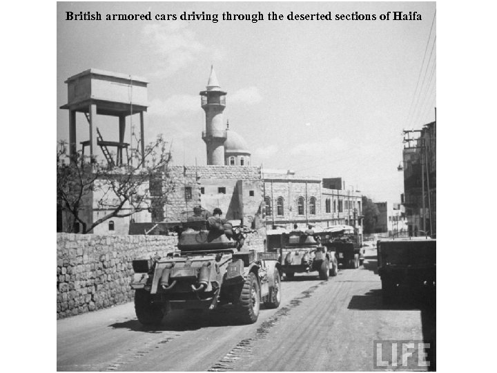 British armored cars driving through the deserted sections of Haifa