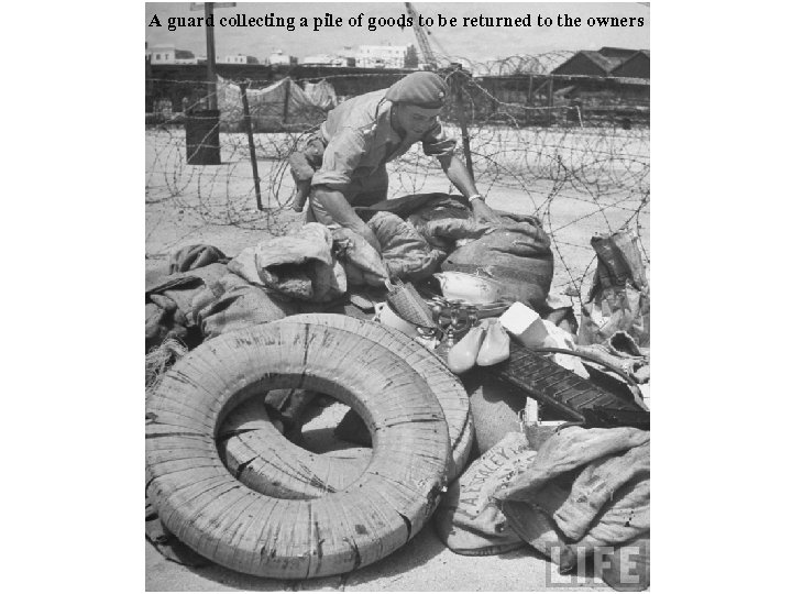 A guard collecting a pile of goods to be returned to the owners