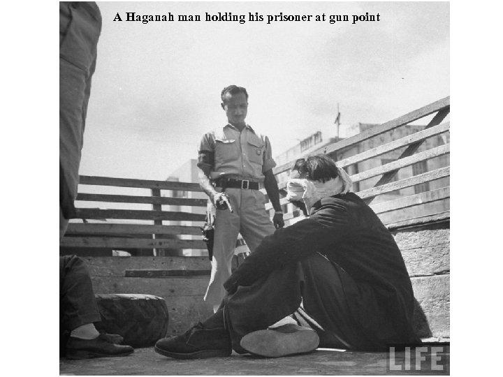 A Haganah man holding his prisoner at gun point