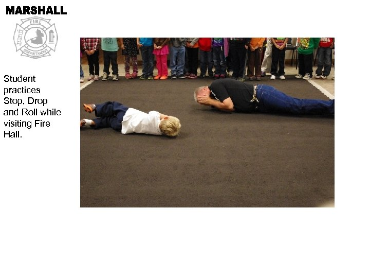 Student practices Stop, Drop and Roll while visiting Fire Hall.