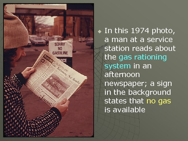 u In this 1974 photo, a man at a service station reads about the