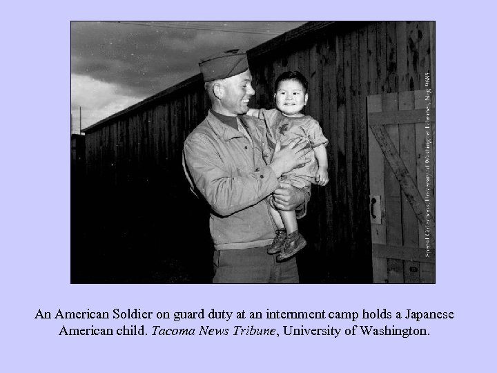 An American Soldier on guard duty at an internment camp holds a Japanese American