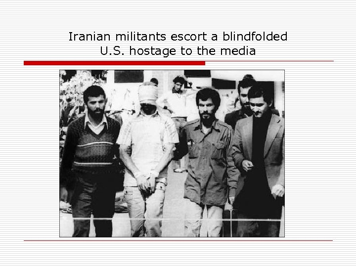 Iranian militants escort a blindfolded U. S. hostage to the media