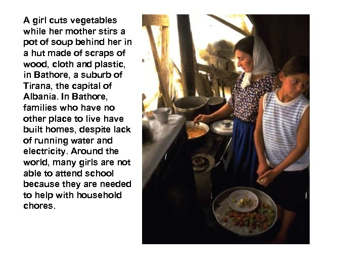 A girl cuts vegetables while her mother stirs a pot of soup behind her