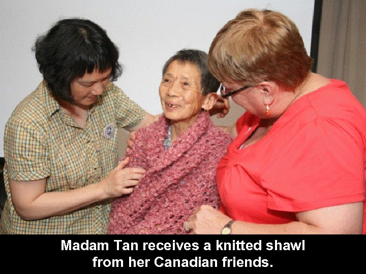 Madam Tan receives a knitted shawl from her Canadian friends.