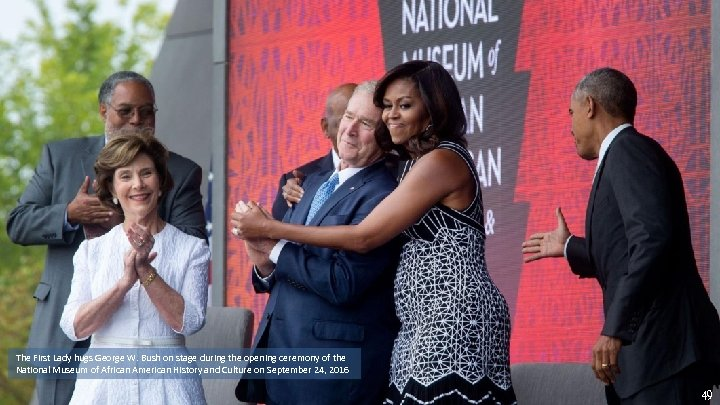 The First Lady hugs George W. Bush on stage during the opening ceremony of