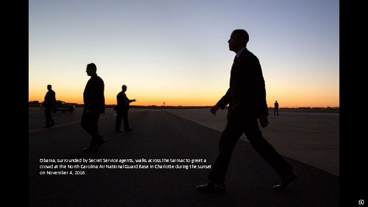 Obama, surrounded by Secret Service agents, walks across the tarmac to greet a crowd