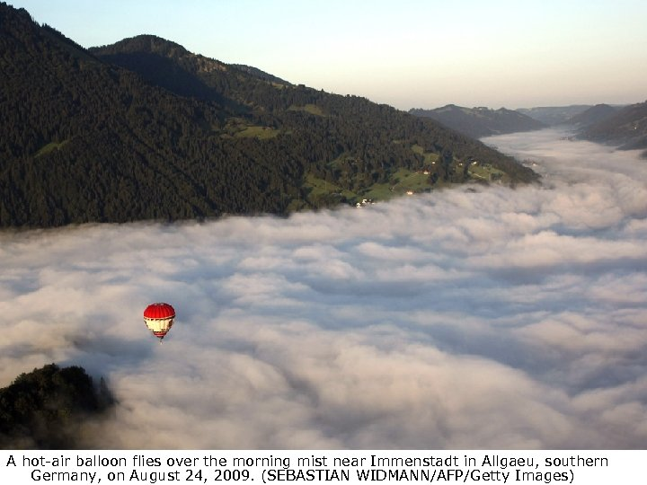 A hot-air balloon flies over the morning mist near Immenstadt in Allgaeu, southern Germany,