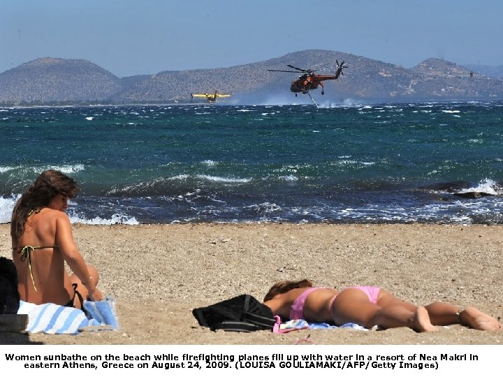 Women sunbathe on the beach while firefighting planes fill up with water in a
