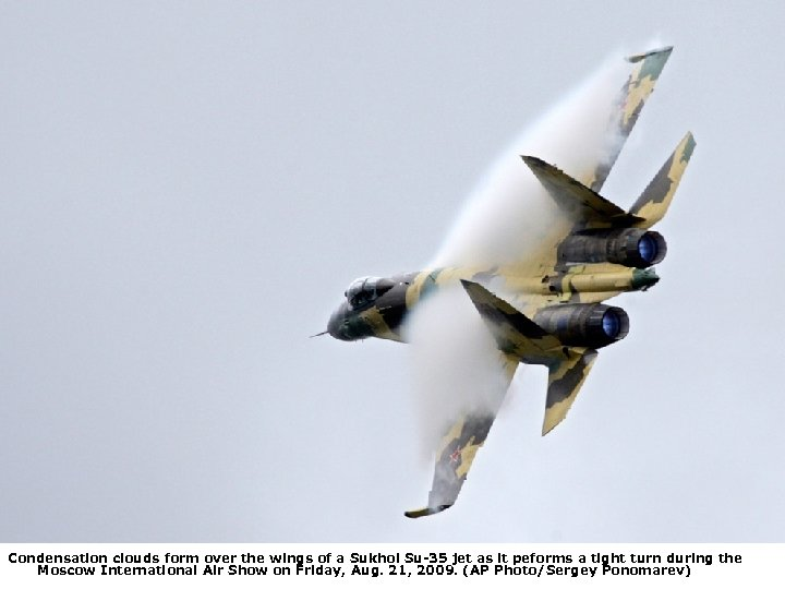 Condensation clouds form over the wings of a Sukhoi Su-35 jet as it peforms