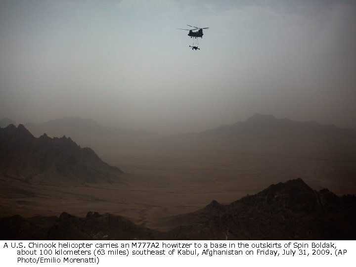 A U. S. Chinook helicopter carries an M 777 A 2 howitzer to a