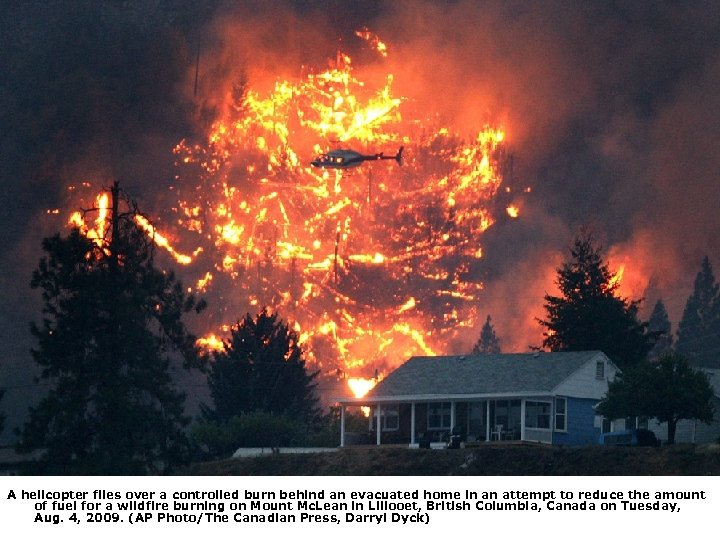 A helicopter flies over a controlled burn behind an evacuated home in an attempt