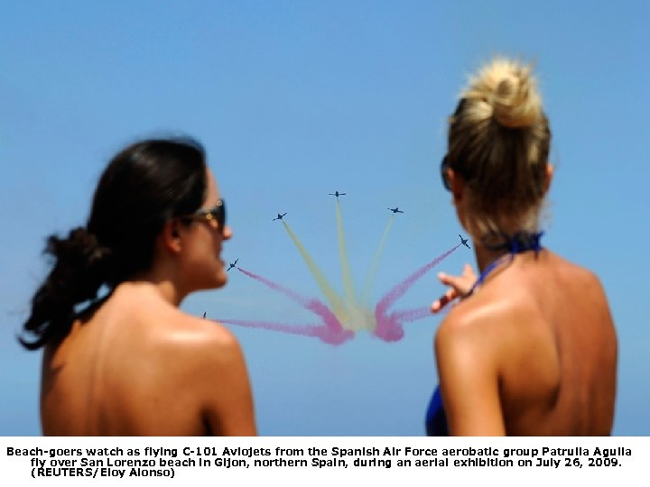 Beach-goers watch as flying C-101 Aviojets from the Spanish Air Force aerobatic group Patrulla