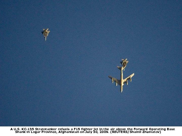 A U. S. KC-135 Stratotanker refuels a F 15 fighter jet in the air