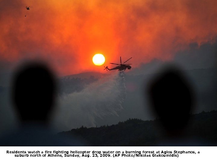 Residents watch a fire fighting helicopter drop water on a burning forest at Agios