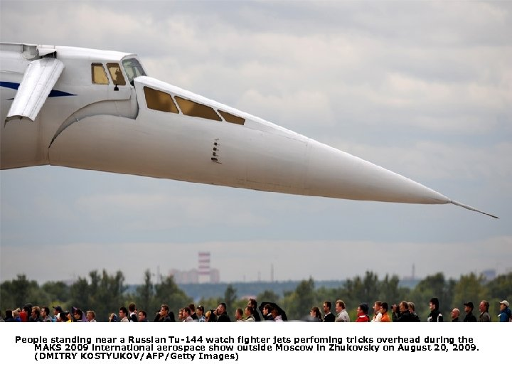 People standing near a Russian Tu-144 watch fighter jets perfoming tricks overhead during the