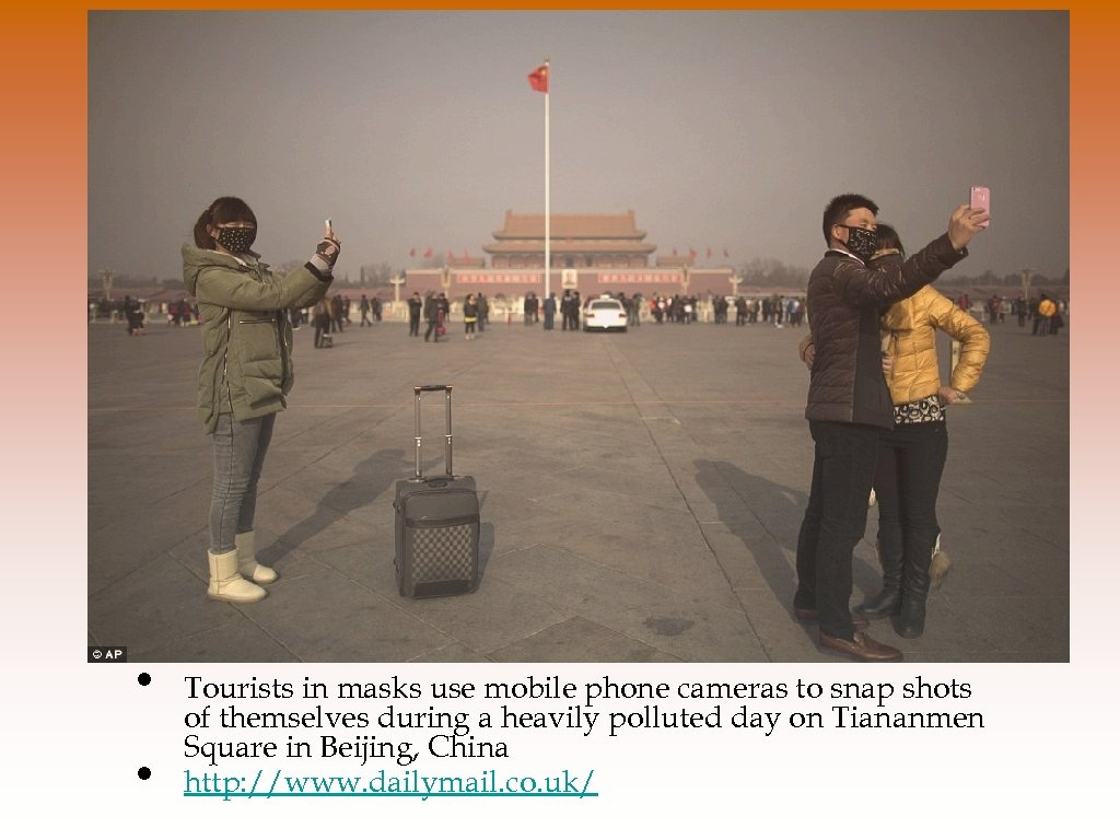 • • Tourists in masks use mobile phone cameras to snap shots of