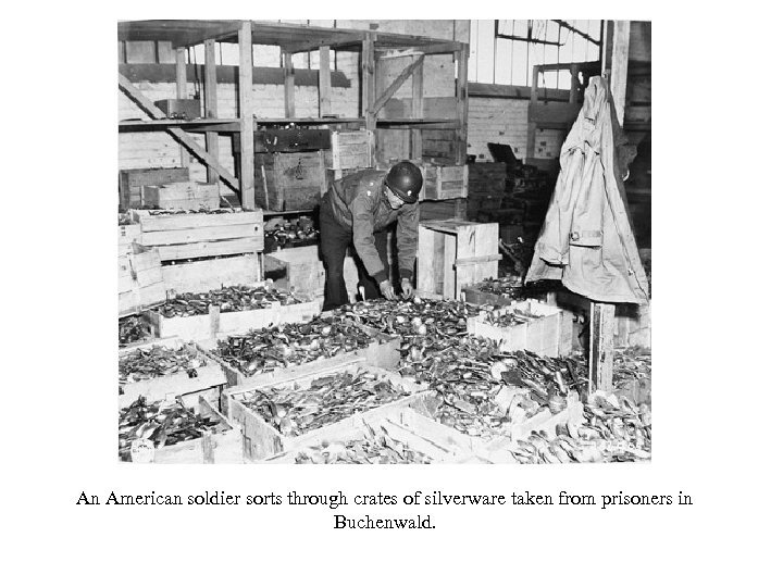 An American soldier sorts through crates of silverware taken from prisoners in Buchenwald.
