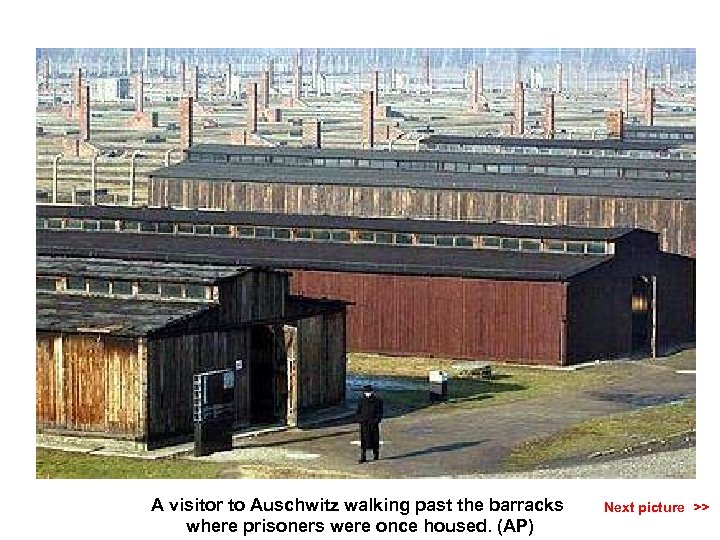 A visitor to Auschwitz walking past the barracks where prisoners were once housed. (AP)