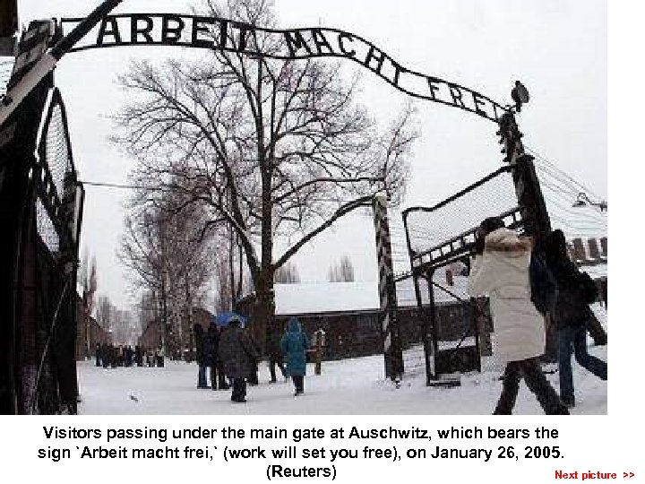Visitors passing under the main gate at Auschwitz, which bears the sign `Arbeit macht