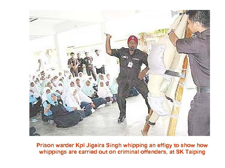 Prison warder Kpl Jigeira Singh whipping an effigy to show whippings are carried out