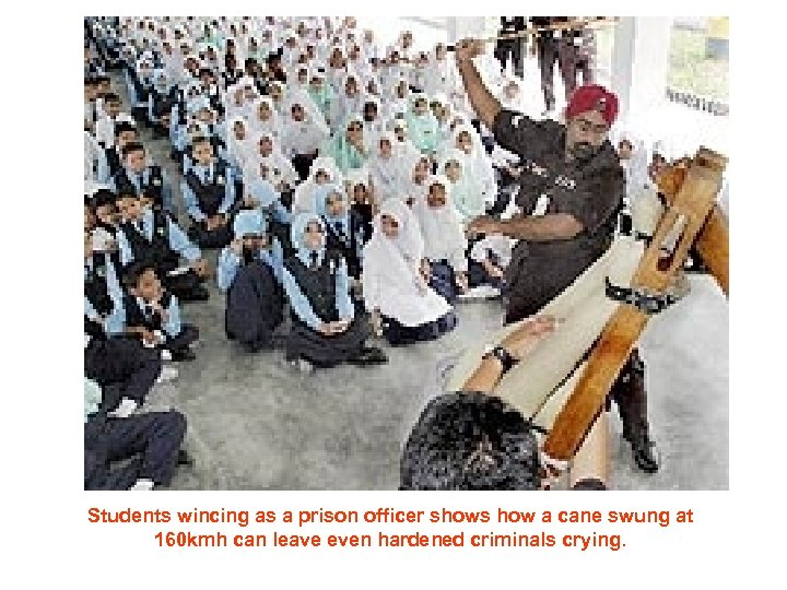 Students wincing as a prison officer shows how a cane swung at 160 kmh