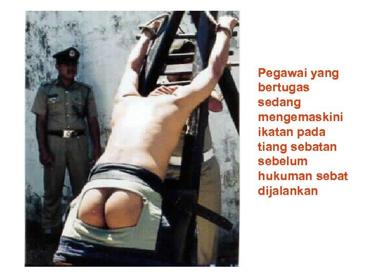 Pegawai yang bertugas sedang mengemaskini ikatan pada tiang sebatan sebelum hukuman sebat dijalankan